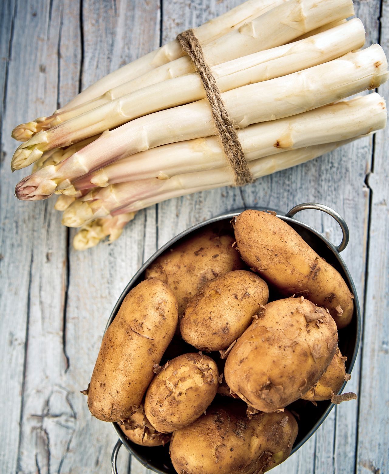 Bundle of Fresh unpeeled white Asparagus and Early Potatoes