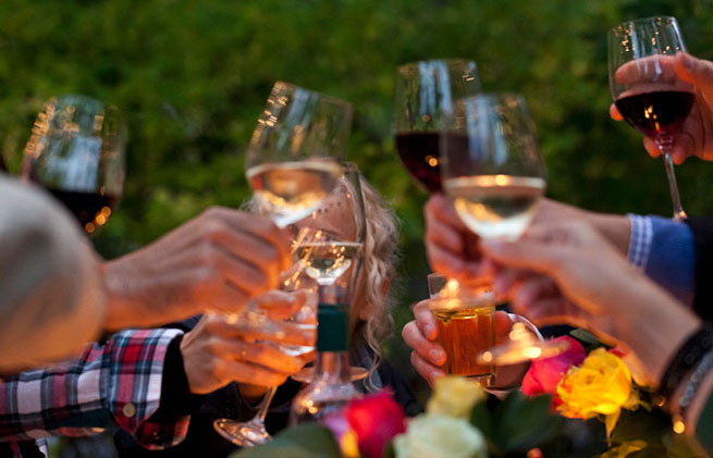 Hands raise wine glass for a toast under a tree with twinkling lights.